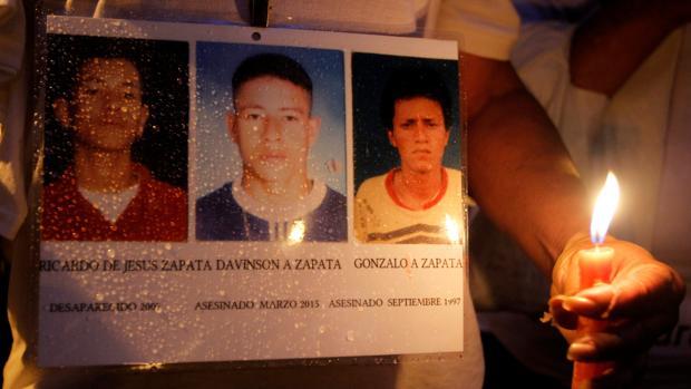 Fotos de desaparecidos o asesinados durante el conflicto interno colombiano, exhibidas durante una marcha por la paz este viernes en Medellín