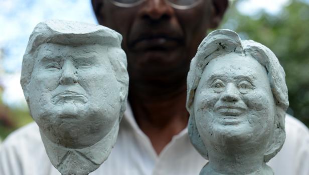 El artista de Sri Lanka Upali Dias posa con dos bustos de los candidatos americanos de su autoría