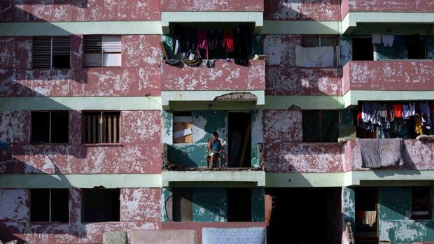 Un cubano sentado en el destruido balcón de su casa, tras el paso del huracán Matthew por Baracoa