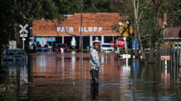 Un hombre permanece de pie en una calle inundada como resultado del paso del huracán Matthew en Fair Bluff, Carolina del Norte