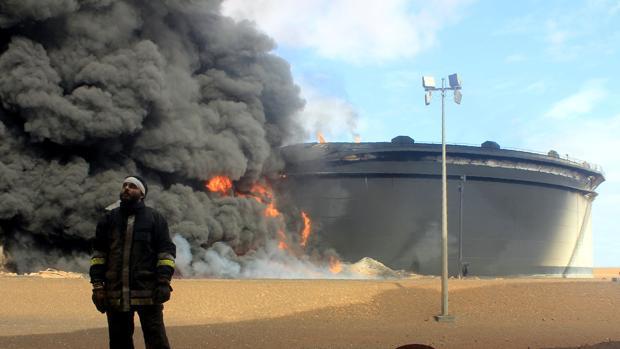 Un bombero junto a tanque de almacenaje de petróleo en llamas en Ras Lanuf