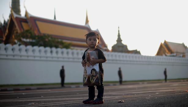 Un niño con la fotografía de la Familia Real junto al Palacio de Bangkok