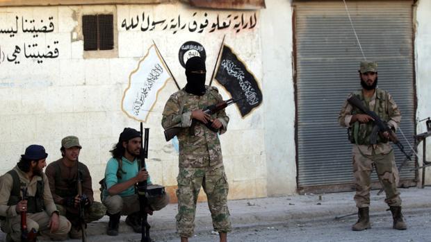 Combatientes rebeldes cerca de graffitis de Estado Islámico y dibujos en una pared en la ciudad de Dabiq, al norte de campo Alepo, Siria