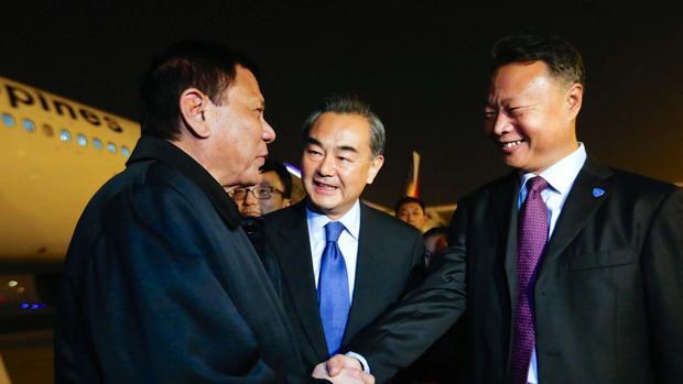 Duterte junto al ministro chino de Exteriores, en el centro, a su llegada a Pekín