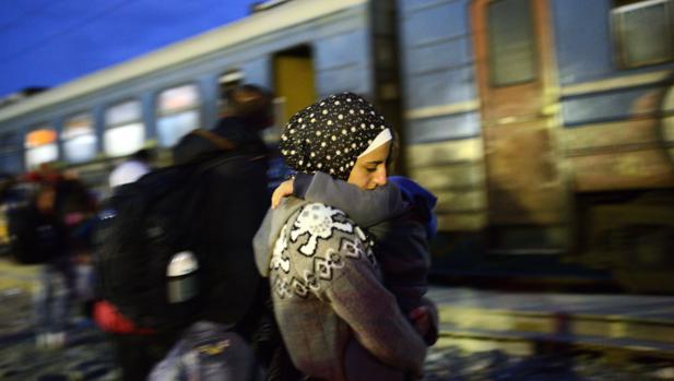 Emigrantes y refugiados esperan a abordar un tren con destino a Serbia en la frontera entre Macedonia y Grecia, cerca de la localidad de Gevgelija