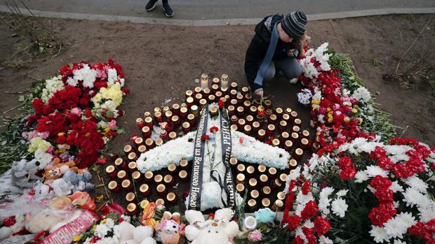 Un niño enciende una vela delante del monumento en memoria de las 224 víctimas asesinadas en el atentado contra un avión ruso sobre el Sinaí, en Vsevolozhks, a las afueras de San Petersburgo (Rusia).