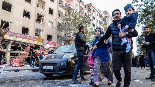 Una familia huye de la zona afectada por un atentado con coche bomba este viernes en Diyarbakir, la «capital» kurda de Turquía