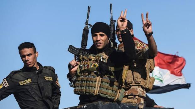 Un grupo de militares iraquíes hacen el signo de la victoria durante su avance hacia Mosul