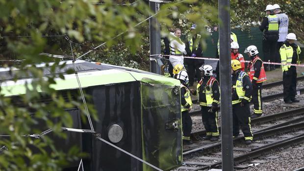 Miembros de los equipos de emergencia trabajan para recatar a las víctimas del tranvía siniestrado este miércoles en Londres