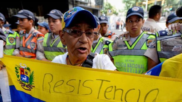 Un manifestante sostiene la bandera nacional de Venezuela durante una marcha protesta contra el gobierno del presidente Nicolás Maduro, en Caracas