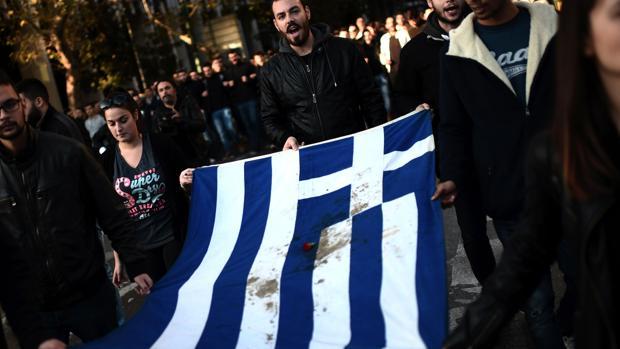 Varios estudiantes lideran la marcha de este jueves con la bandera griega manchada de sangre, símbolo de la revuelta que se produjo en el país heleno en 1973