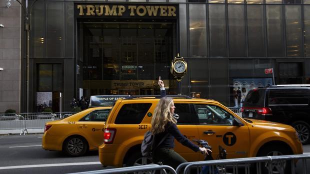 Una mujer realiza una seña obscena frente al edificio Torre Trump