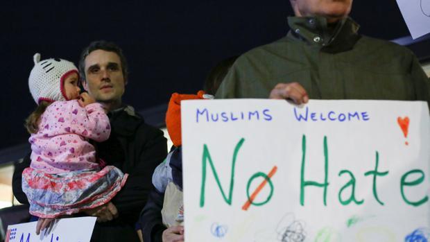 Manifestantes sostienen pancartas de protesta contra el presidente elcto, Donald Trump, y en apoyo a los musulmanes este lunes en Hamtramck, Michigan