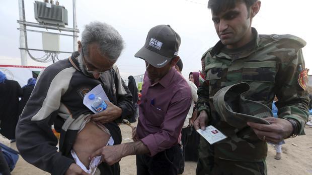 Un soldado iraquí observa las heridas de un desplazado por la guerra en el campo de refugiados de Mosul, capital de la provincia de Nínive