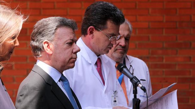 El presidente de Colombia Juan Manuel Santos escucha al médico Adolfo Llinás mientras lee los resultados médicos de los exámenes a los que fue sometido el presidente, en la clínica Santa Fe de Bogotá