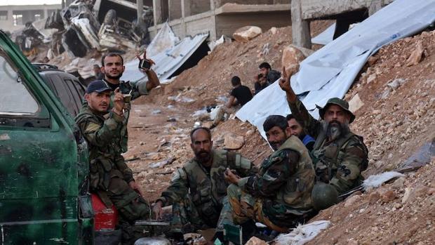 Un grupo de soldados sirios almuerzan tras recuperar una zona residencial de Alepo
