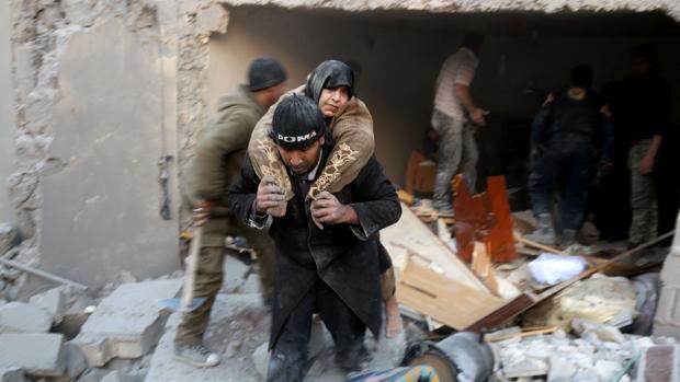 Una mujer es rescatada entre los escombros tras un bombardeo sobre el distrito rebelde de al-Hamra, el pasado domingo en Alepo