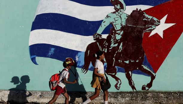 Colegiales cubanos pasan junto a un mural con la bandera del país, este martes en La Habana