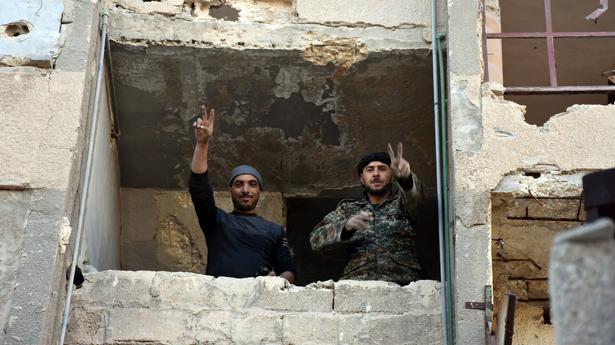 Soldados del Ejército sirio hacen el signo de la victoria desde un edificio destruido por las bombas en Masaken Hanano, una zona del este de Alepo recuperada por las fuerzas de Al Assad