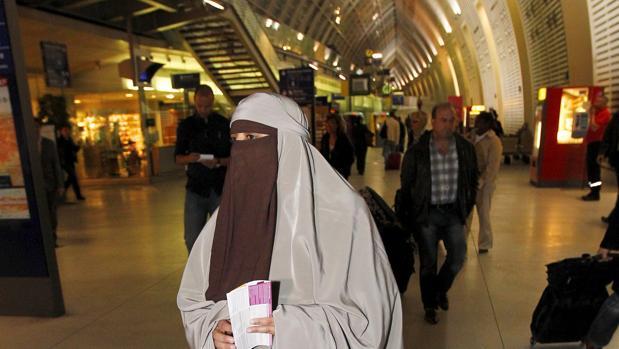 Una mujer vestida con un niqab camina por una estación de trenes