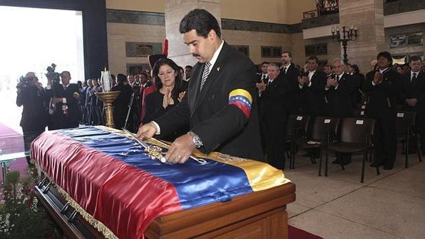 Nicolás Maduro entrega a Hugo Chávez la espada de Simón Bolívar durante el funeral