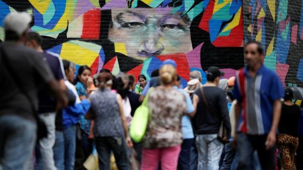 Ciudadanos venezolanos hacen cola para comprar comida en una tienda en Caracas, Venezuela,