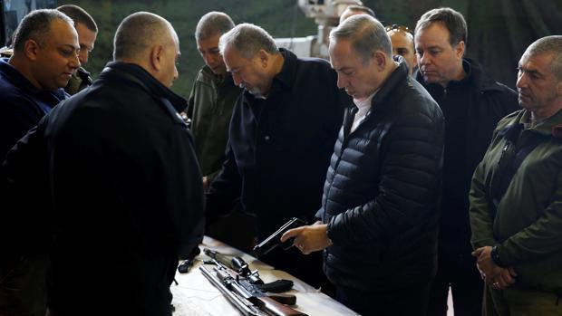 Benjamin Netanyahu sostiene una pistola que el Ejército israelí asegura que confiscó en Cisjordania, durante una visita el martes a la base militar del asentamiento de Beit El near, cerca de Ramala