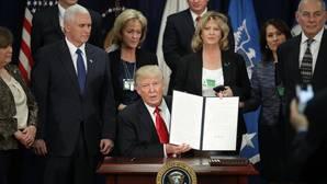 El presidente estadounidense, Donald J. Trump (c), enseña la firma de la orden ejecutiva para destinar fondos federales a la construcción del muro con México durante una ceremonia en el Departamento de Seguridad Nacional en Washington