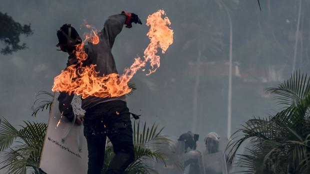 Un opositor a Nicolás Maduro se enfrenta a la Guardia Nacional Bolivariana durante las protestas en Caracas