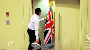Un funcionario lleva una bandera del Reino Unido, en la sede de la CE en Bruselas