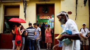 Un grupo de personas, junto a la puerta de un restaurante privado en La Habana