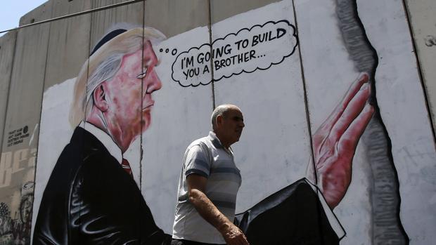 Un hombre pasa por delante del graffiti del presidente de los Estados Unidos, Donald Trump, en el muro de Belén