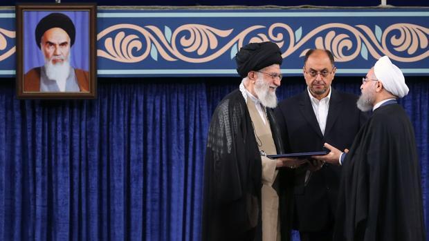 El presidente de Irán, Hasan Rohaní (d), recibe un certificado sobre su nombramiento de manos del líder supremo iraní, el ayatolá Alí Jameneí (i), durante una ceremonia en Teherán