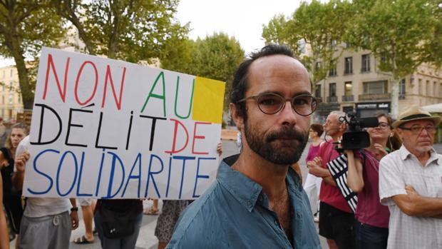 """El agricultor francés Cedric Herrou, a la entrada del palacio de justicia en Aix-en-Provence cerca de un letrero que dice """"No al crimen de solidaridad"""""""