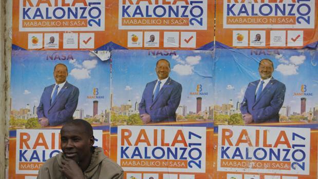 Un hombre descansa junto a un cartel electoral del líder opositor keniata Raila Odinga en Nairobi