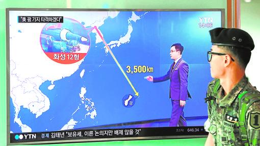 Un soldado surcoreano pasa junto a una pantalla en la que se puedever la distancia entre Pyongyang y la isla de Guam