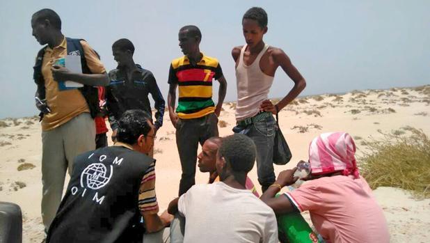 Un trabajador de la Organización Internacional para las Migraciones ayuda a migrantes que fueron obligados a arrojarse al mar en una una playa en shabua (Yemen)