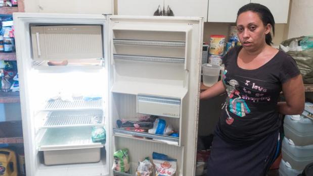 Un ama de casa venezolana muestra su nevera casi vacía