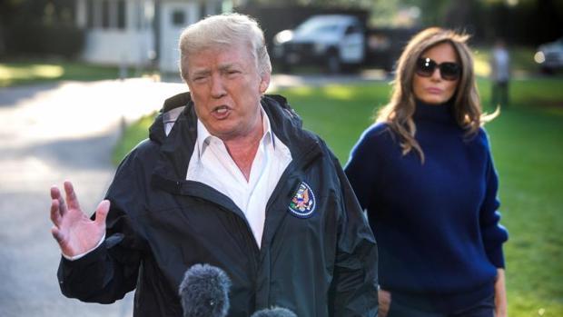 El presidente de EE.UU., Donald Trump, con su mujer, habla con los medios poco antes de partir este martes hacia Puerto Rico