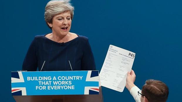Un manifestante interrumpe el discurso de Theresa May en la convención anual tory y le entrega un ejemplar del formulario P45 (carta de despido para los trabajadores), este miércoles en Mánchester