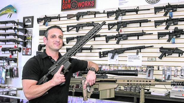El propietario de una tienda de armas en Palm Beach, Florida, junto a su mercancía