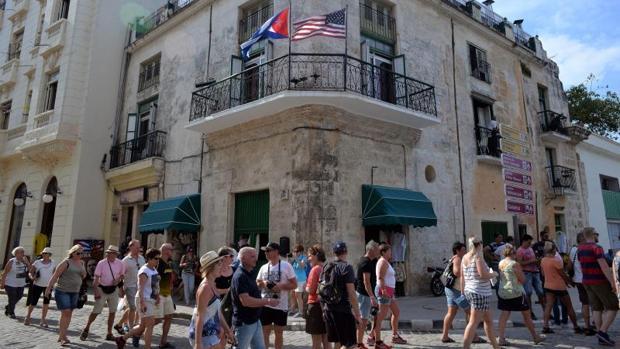Un grupo de turistas junto a un edificio de La Habana con las banderas de EE.UU. y Cuba, poco antes del viaje de Barack Obama a la isla