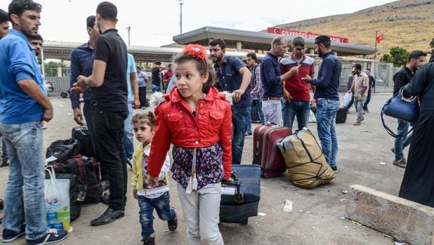 Varias familias sirias se llevan sus pertenencias mientras cruzan la puerta fronteriza al lado turco el 9 de octubre de 2017 en el distrito de Reyhanli en Hatay