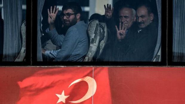 Familiares de las víctimas del enfrentamiento en el Pueente del Bósforo saludan desde el interior de un autobus a su llegada al juicio