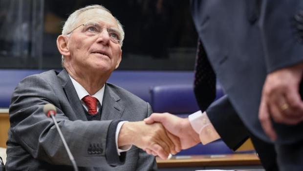 El titular de Finanzas alemán, Wolfgang Schäuble (i) estrecha la mano de su homólogo luxemburgués, durante una reunión de ministros de la Eurozona en Luxemburgo