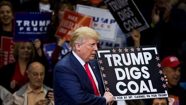 Donald Trump CON un cartel de apoyo a la industria del carbón durante un acto de campaña el pasado año