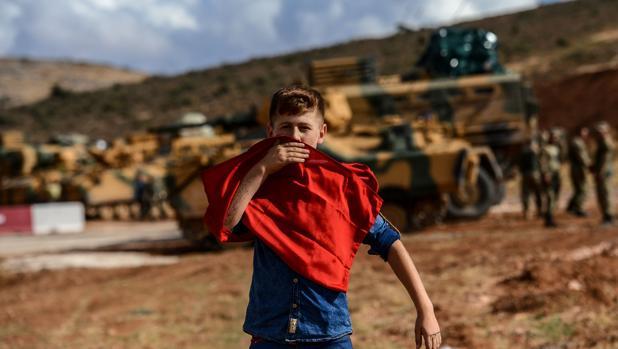 Un joven besa una bandera nacional turca mientras se acerca a los soldados y vehículos blindados turcos durante una manifestación en apoyo de la operación de Idlib del ejército turco cerca de la frontera entre Turquía y Siria, cerca de Reyhanli, Hatay
