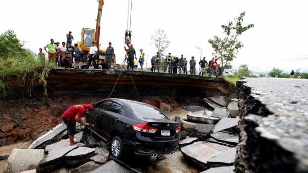 Oficiales tailandeses rescatan un coche en un paso derrumbado