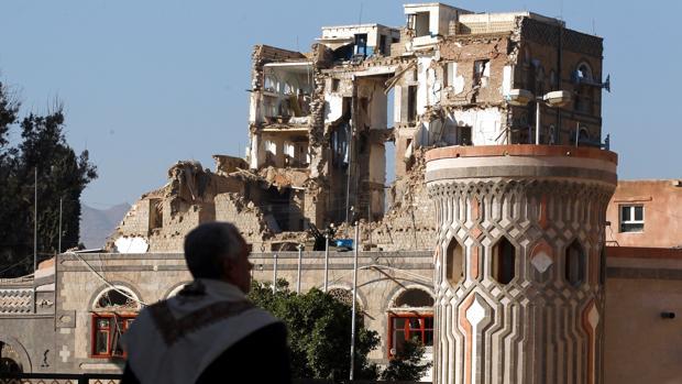 Un hombre se detiene ante lo que queda del Palacio Republicano tras ser alcanzado durante un ataque aéreo lanzados por la coalición militar liderada por Arabia Saudí después de que rebeldes yemeníes mataran ayer al expresidente Ali Abdalá Saleh, en Saná