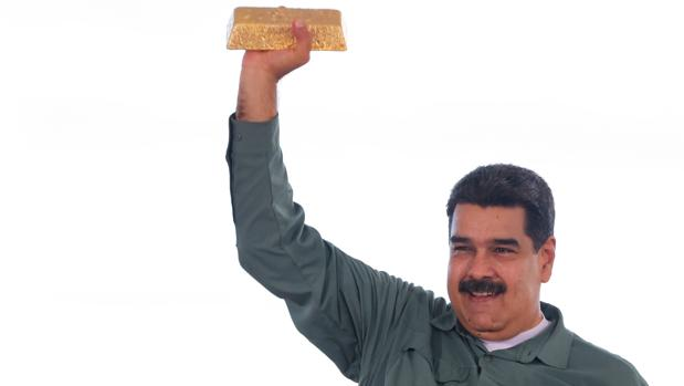 Nicolás Maduro sostiene un lingote de oro para defender el Petro, la criptomoneda venezolana que anunció